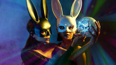 Portrait of two young cute Asian women in black and white rabbit mask posing with small disco ball on the neon lights