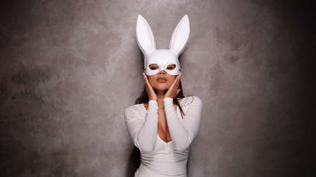 Portrait of beautiful flirting Asian woman in white dress and rabbit mask playfully posing for camera in the spotlight Imagens