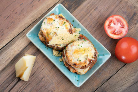 Pan fried crispy eggplant with parmesan cheese crust isolated on wooden table Imagens