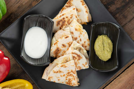 A toasted tortilla with chicken, peppers, red onion and mozzarella served with a guacamole dip and sour cream isolated on wooden table