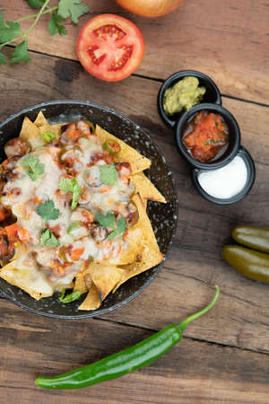 A plate of delicious corn chips nachos in cheddar cheese with beans, tomato, green chili, black olives, cilantro served with guacamole, sour cream and tomato salsa dip on the side isolated on the wooden table Imagens