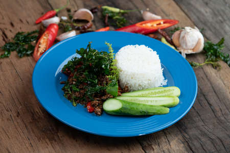 Rice with stir-fried minced pork and basil with cucumber isolated on wooden rustic table