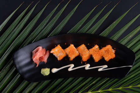 Top view of avocado, crab stick, cucumber, mayonnaise and ebiko sushi isolated on black table with tropical leaves
