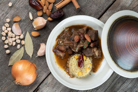 Slow cooked lamb with potato and dates served with warm couscous and chickpeas isolated on the wooden table Imagens