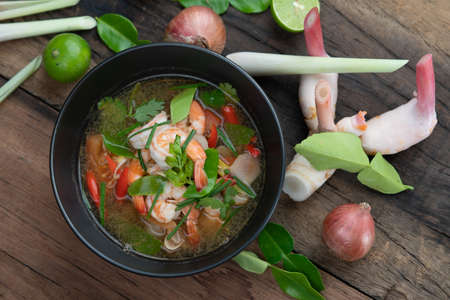 Traditional spicy prawn soup with galangal, lemongrass, kaffir lime leaf and straw mushrooms isolated on the wooden table Imagens