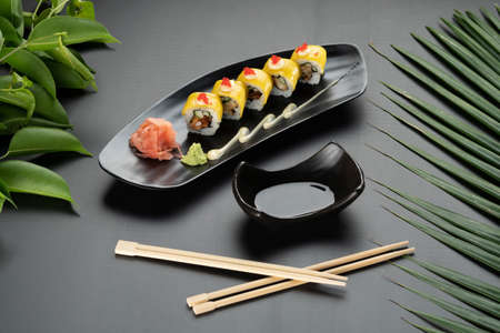 Deep-fried soft-shell crab, cucumber, mango, mayonnaise and tobiko isolated on black table with tropical leaves