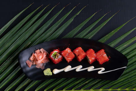 Deep-fried prawns, avocado, mayonnaise and tobiko sushi isolated on black table with tropical leaves