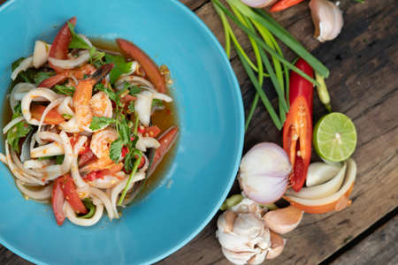 Thai spicy seafood salad with prawns, squid and Thai mussels isolated on wooden table
