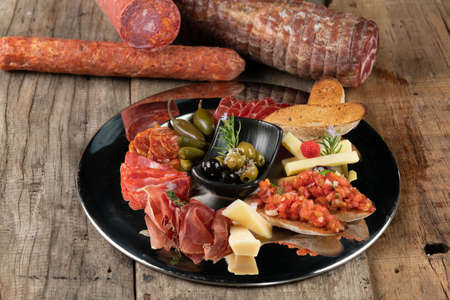 An assortment of cold appetizers served on a black plate isolated on rustic wooden table