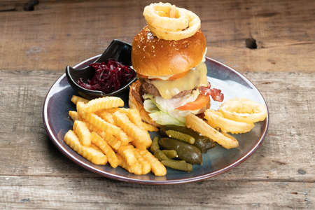 Big burger with beef, bacon, tomato, cheese, lettuce and onion served with french fries, onion rings, pickles and beetroot salad on the side isolated on rustic wooden table