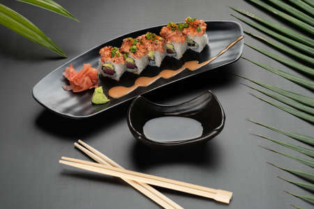 Sushi Roll - Maki Sushi made of tuna, avocado, mayonnaise and ebiko sushi isolated on black table with tropical leaves