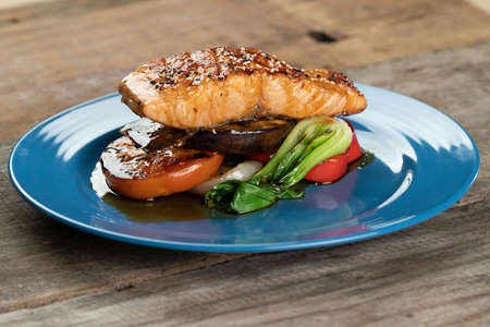 Grilled Salmon steak with vegetables isolated on rustic wooden table