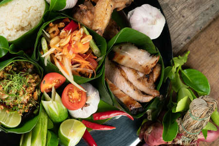 Set of Thai style food with rice, minced pork, papaya salad, pork steak and spare ribs served in banana leaves isolated on wooden table