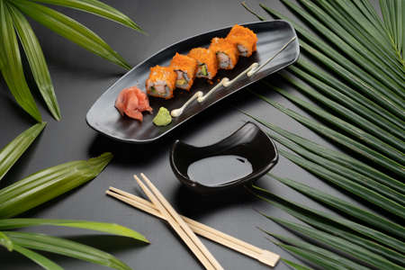 Avocado, crab stick, cucumber, mayonnaise and ebiko sushi isolated on black table with tropical leaves