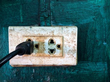 Old electric plug socket on old wall.
