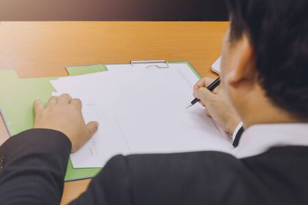 Business man hand signing on document ,Asian men are doing business in the office, Business concept and contract signing