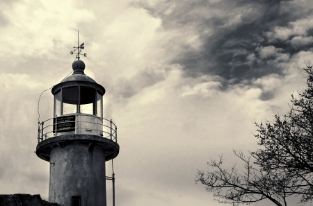 old lighthouse.In black and white with dramatic clouds . photo