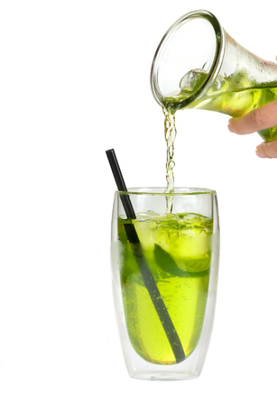 glass of  iced tea with lemon slices and mint leaves isolated on white background