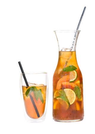 té helado: jarra de té helado sudoroso rodajas de cítricos de limón, naranja y hojas de menta aisladas sobre fondo blanco