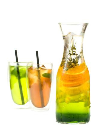 ice lemon tea: sweaty pitcher of iced tea citrus slices lime, orange and mint leaves isolated on white background