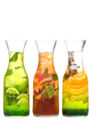 té helado: lanzadores sudorosas de té helado rodajas de cítricos de limón, naranja, pomelo, limón y hojas de menta aisladas sobre fondo blanco Foto de archivo