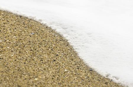 closeup of sea foam with fine sand