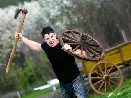 portrait of attacking young man with an ax in his hand