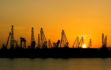 sunset over the industrial area with cranes.Port Varna