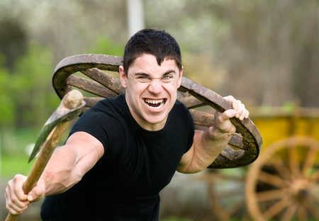 portrait of angry attack young man with an ax in his hand