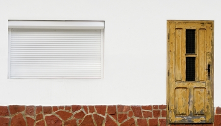 white wall with old wooden door and window with external blinds