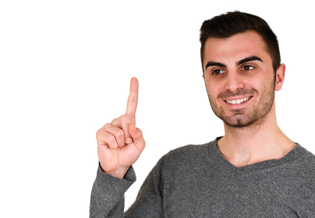smiling young man with beard pointing finger upwards on a white background isolation