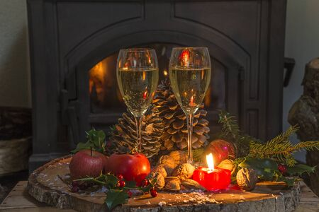 Celebration concept. Two glasses of champagne in front of the burnig wooden stove