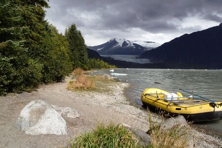 Alaskan lake view with floating ice and inflateable boat