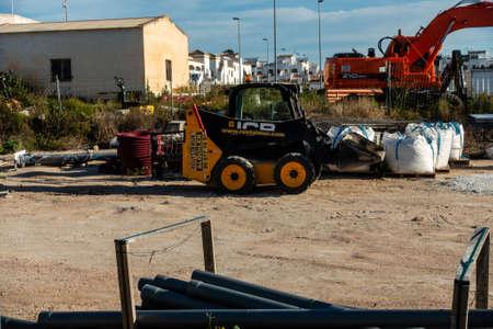 Torrevieja, Valenciana, Spain - May 02 2020 : mini jcb digger in builders yard on urbanisation in spain Редакционное