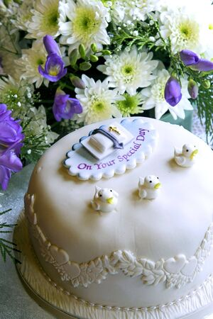 cake with icing: A christening cake in front of a flower arrangement