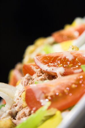 Close up of a fresh tuna salad isolated against a black background photo