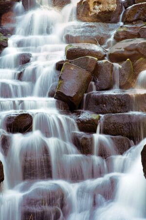 Scenic waterfall with water flowing over rocks Stock Photo