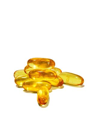 Vitamin oil capsules isolated against a white background