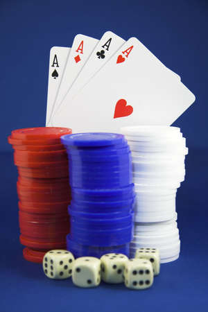 jack pot: Four aces shown with chips and poker dice set against a white background Stock Photo
