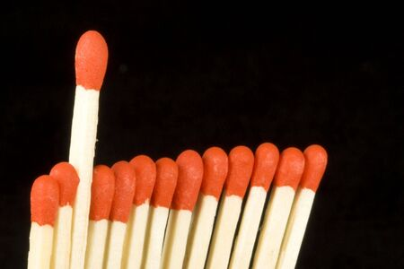 One red tipped match standing out from a bundle