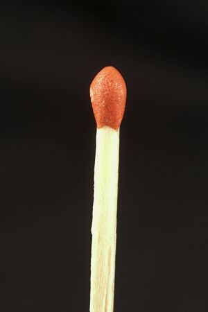 Single red tipped matchstick isolated against a black background Stock fotó
