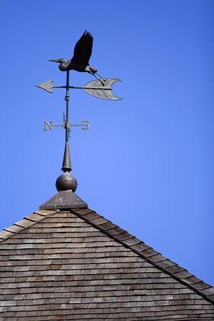 vane: Bird weather vane on roof set against blue sky Stock Photo