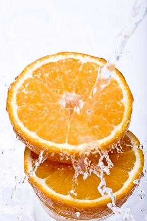 Water splashing down on an orange