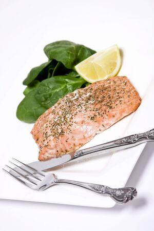 Salmon fillet with herbs macro with spinach and lemon wedge