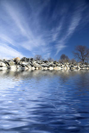 Frozen shoreline with iced rocks and blue sky