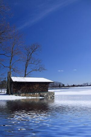 log cabin winter: Cabin on a frozen lake with a vivid blue sky Stock Photo