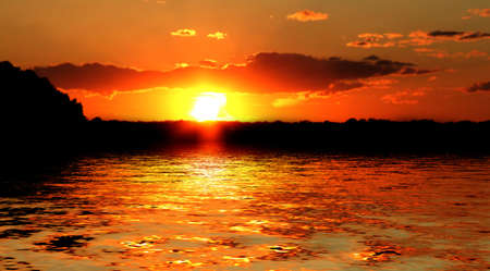 Sun setting over a reflective body of water Stock Photo - 2515674