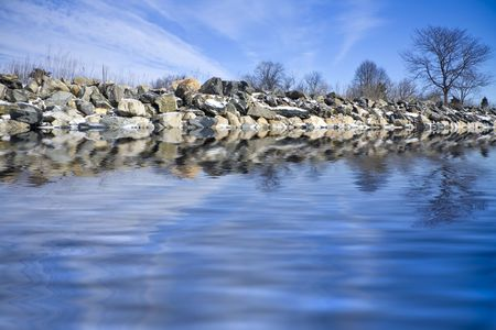 Frozen shoreline with iced rocks and blue sky Stock Photo - 2538917