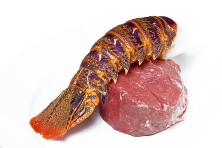 Raw lobster and fillet steak on a white plate photo