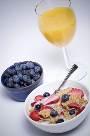 Cereal with blueberries and fresh orange juice with vignetted background photo